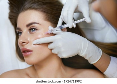 Face Injection. Anti Aging Biorevitalization In Cosmetic Salon.Young Girl Is Receiving Hyaluronic Acid Skincare. Beautician Hands With Filler In Syringe Closeup.