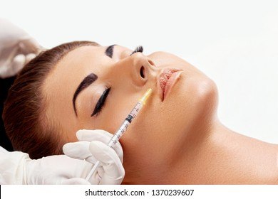 Face Injection. Woman getting cosmetic injection of botox in lips, closeup. Lip Augmentation. Portrait of beautiful Female with soft skin, perfect Makeup Receiving Facial skin lifting treatment,