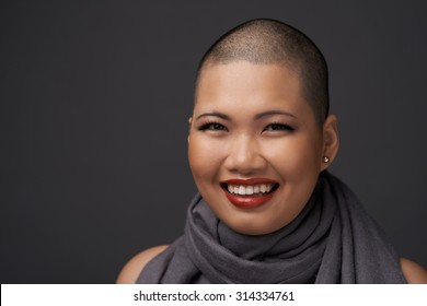 Face of laughing Vietnamese woman with shaved hairstyle