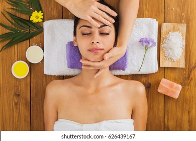 Face lifting and body massage to beautiful girl in cosmetology cabinet or beauty parlor. Top view