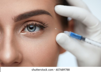 Face Lifting. Portrait Of Beautiful Woman's Face With Perfect Smooth Skin Receiving Hyaluronic Collagen Injection. Closeup Of Doctor Hands In Gloves Holding Syringe Near Woman Eye. High Resolution
