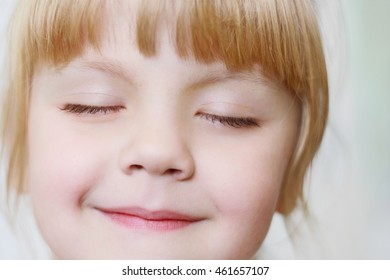 Face of a little girl with closed eyes close-up