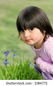 Face of a little girl sitting on the grass in spring next to some bluebell flowers.