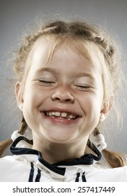 face of a little girl smiling with plaits and closed eyes