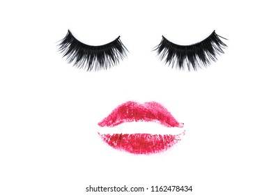 The face is made of red lipstick kiss and two false eyelashes. On a white background