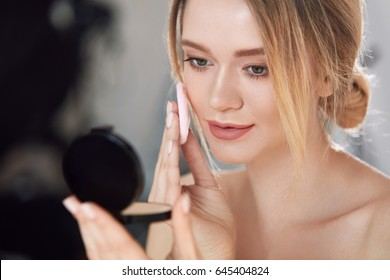 Face Make-Up. Closeup Of Sexy Female Applying Dry Powder Foundation Looking In Mirror. Portrait Of Young Woman Putting Makeup Powder With Cosmetic Cushion On Her Facial Skin Indoors. High Resolution
