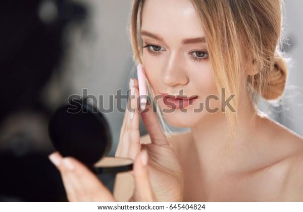 化粧。鏡を見ながらドライパウダーファンデーションを塗るセクシーな女性の接写。室内で化粧用のクッションを付けた化粧粉を身にまとった若い女性のポートレート。高解像度