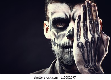 Face of man with Halloween skull makeup on the black background