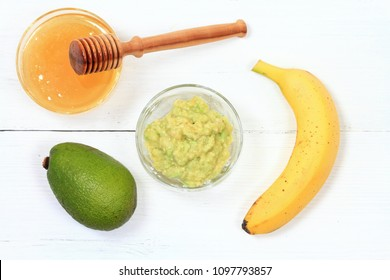Face mask from avocado, yogurt, banana  and honey. Ingredients for facial mask on the white wooden board, top view