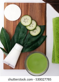 face mask with cucumber slices, dark wood background