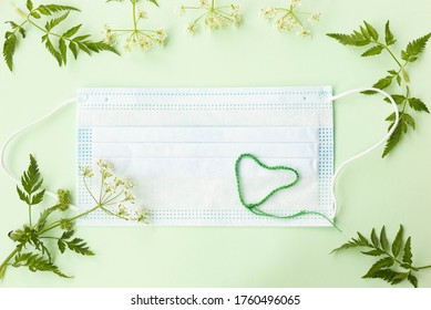 Face mask, flowers and crochet heart on light green background. Hemlock-parsley (Conioselinum boreale) flowers top vie flatlay. Concept of social distancing during covid pandemy.