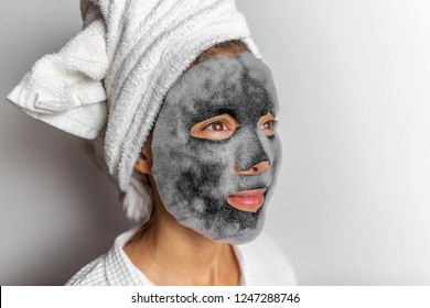 Face mask foam bubbles charcoal detox facial treatment at home -asian girl purifying skin removing dead skin cells with chemical peel korean face sheet in bathroom.