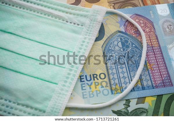 Gesichtsmaske auf Euro-Banknoten-Hintergrund. Der weltweite Ausbruch des neuartigen Coronavirus (Covid-19) wirkt sich auf die EU, die Weltwirtschaft, die Finanzkrise, Investitionen und den Aktienmarkt aus. Eine Koronavirus-Pandemie in Europa.
