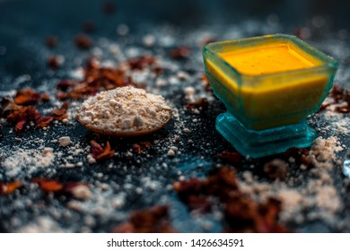 Face mask for skin whitening on wooden surface consisting of besan or gram flour and some rose water. With some dried rose petals and gram flour spread on the surface.