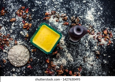 Face mask for skin whitening on wooden surface consisting of besan or gram flour and some rose water. With some dried rose petals and gram flour spread on the surface. Horizontal top shot.