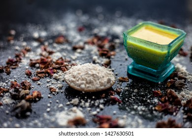 Face mask for skin whitening on wooden surface consisting of besan or gram flour and some rose water. With some dried rose petals and gram flour spread on the surface. Horizontal shot.
