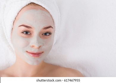 Face mask, spa beauty treatmen with copy space. Woman applying facial clay mask at spa salon, skincare, top view, overhead