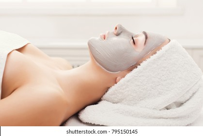 Face mask, spa beauty treatment. Woman applying facial clay mask at spa salon, skincare, side vies