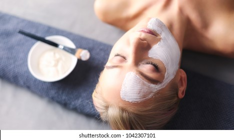 Face mask.Beautiful young girl at spa ,cosmetician woman applying facial mask