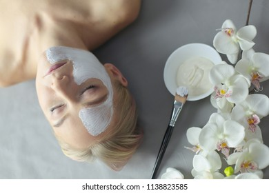 Face mask.Beautiful young girl at spa ,cosmetician woman applying facial mask.