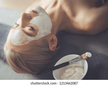 Face mask.Beautiful young girl at spa ,cosmetician woman applying facial mask.