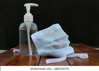 Face masks and hand sanitizer bottle on wood table for peple washing hands to help stop spreading outbreak coronavirus covid-19 for public health safety