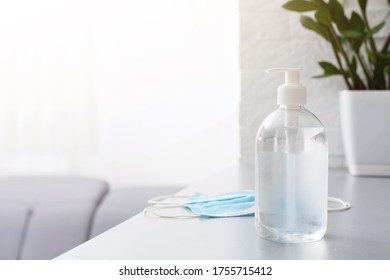 Face masks and hand sanitizer bottle on table for peple washing hands to help stop spreading outbreak coronavirus covid-19 for public health safety