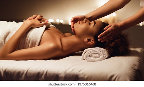 Face massage. African-american woman getting spa treatment, side view