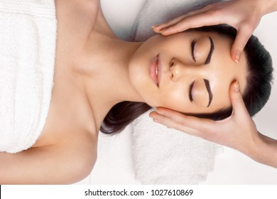 Face massage.  Close-up of young woman getting spa massage treatment at beauty spa salon.Spa skin and body care. Facial beauty treatment.Cosmetology.