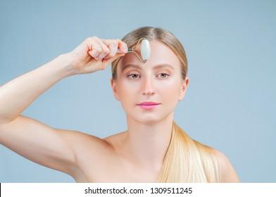 Face massage. Facial beauty treatment. Beautiful woman getting massage face using roller massage