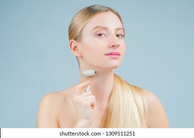 Face massage. Facial beauty treatment. Beautiful woman getting massage face using roller massage