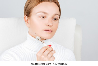 Face massage. Facial beauty treatment. Beautiful woman getting massage chin using roller massage