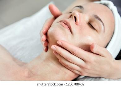 Face massage. Facial skincare. Hands of masseur. Woman at beauty spa salon. Skin Moisturizing Procedure