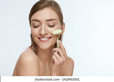 Face massage. Smiling woman using jade facial roller for skin care, beauty treatment on white isolate background. Girl using natural massager closeup portrait