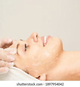 Face massage at spa salon. Doctor hands. Pretty female patient. Beauty treatment. Healthy skin procedure. Young woman head. Light background. Scrub rejuvenation. Facial dermatology mask. Detox therapy