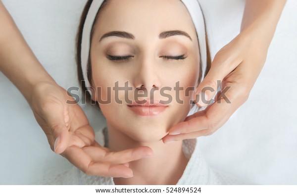 Gesichtsmassage. Haut- und Körperpflege heilen. Nahaufnahme von jungen Frauen, die im Schönheitssalon Wellness-Massage erhalten. Schönheitspflege des Gesichtes.