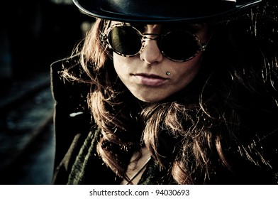 Face of mystery brunette woman wearing dark glasses and a hat, dark closeup outdoor portrait.