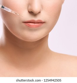Face needle injection. Young woman cosmetology procedure. Doctor gloves.