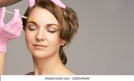 Face needle injection. Young woman cosmetology procedure. Doctor gloves. Brow.