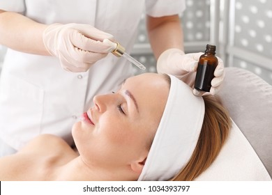 Face oil. The beautician applies the cosmetic to the face
