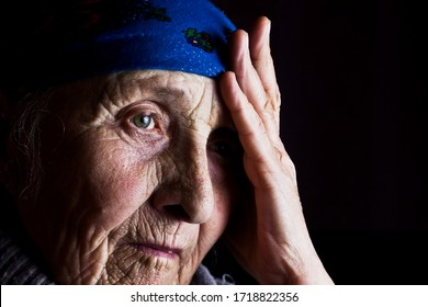 Face of an old grandmother portrait photo. Granny. The wrinkled face of an aging mother. Grandmother looks into the distance with hope. An elderly woman is bored alone.