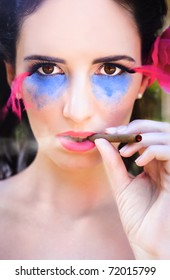 Face On Portrait Of Attractive Young Woman Wearing Glamorous Makeup Smoking Cigar Outdoors