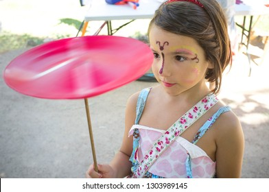 Face painted child girl playing with spinning plate. Classic toys concept