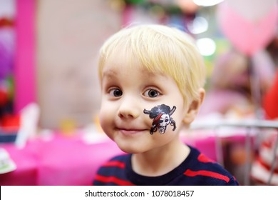 """Face painting for cute little boy during kids merriment. Face paint for """"Pirates"""" theme on birthday party. Preschooler kids celebrating party in entertainment center"""