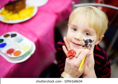 "Face painting for cute little boy during kids merriment. Face paint for ""Pirates"" theme on birthday party. Preschooler kids celebrating party in entertainment center"