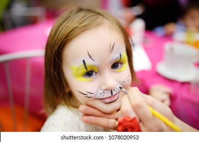 "Face painting for cute little gorl during kids merriment. Face paint for ""Animals"" theme on birthday party. Preschooler kids celebrating party in entertainment center"