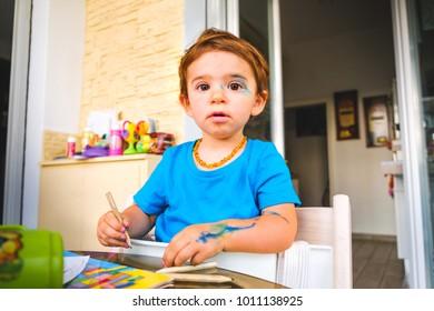 face paints Mischievous baby blue color markers innocent face painted child .