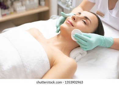 Face of peaceful young lady in white towel lying with closed eyes and smiling while having her face cleaned with cotton pad