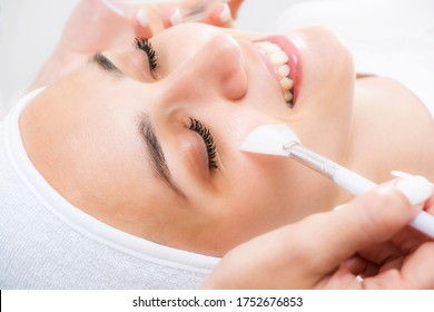 Face peeling at the beautician. Facial treatments. Photo chemical, glycolic, almond peeling.