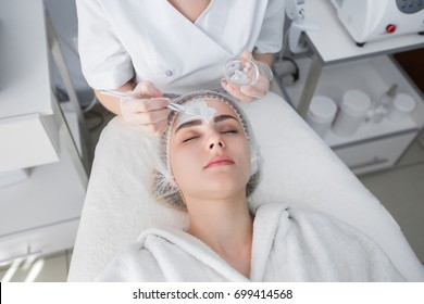 Face peeling mask, spa beauty treatment, skincare. Woman getting facial care by beautician at spa salon